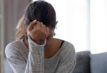 Young woman crying in her living room experiencing postpartum depression after being adopted