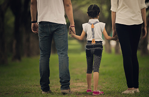 Image of a man and woman walking while holding a child's hands